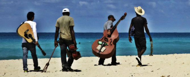 musicians walking along Havana beach