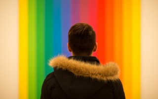 rainbow background with young person in foreground